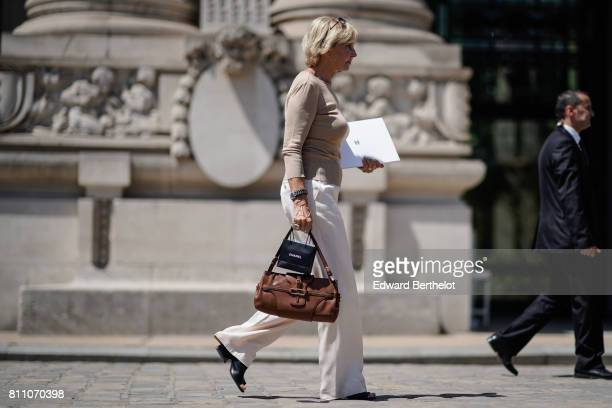 A guest wears a camel pull over white flare pants black shoes a brown bag outside the Chanel show during Paris Fashion Week Haute Couture Fall/Winter...