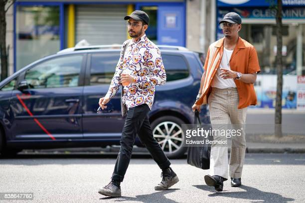 A guest wears a cap a colored shirt blue pants gray shoes a guest wears an orange shirt a white tshirt flare pants outside the Y/Project show during...