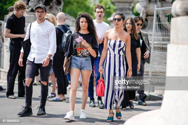 A guest wears a cap a white shirt ripped black jeans a guest wears a black tshirt blue denim shorts white sneakers a guest wears sunglasses an...