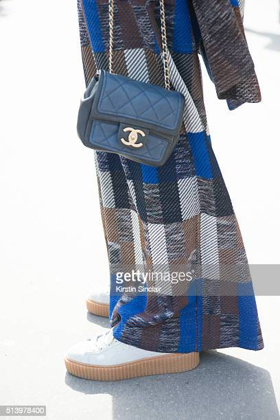 Guest wears a Chanel bag Puma shoes and Coven look on day 5 during Paris Fashion Week Autumn/Winter 2016/17 on March 5 2016 in Paris France