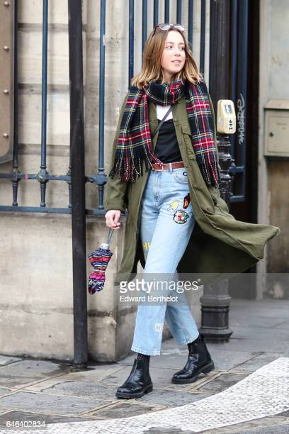 A guest wears a checked scarf a green long coat blue denim jeans pants black boots a black low neck top and a brown belt outside the JOUR/NE show...
