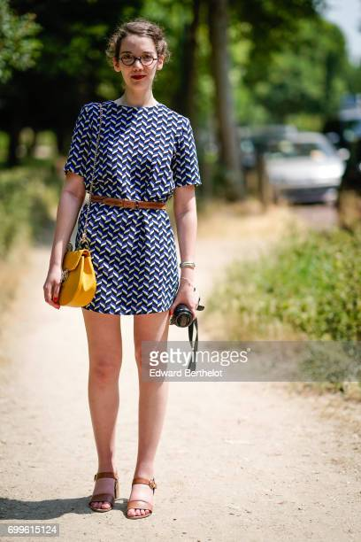 A guest wears a dress a belt and a yellow bag outside the Balenciaga show during Paris Fashion Week Menswear Spring/Summer 2018 on June 21 2017 in...