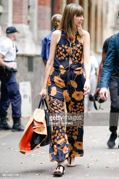 A guest wears a flower print silk outfit made of a sleeveless top and flared pants outside the Paul Smith show during Paris Fashion Week Menswear...