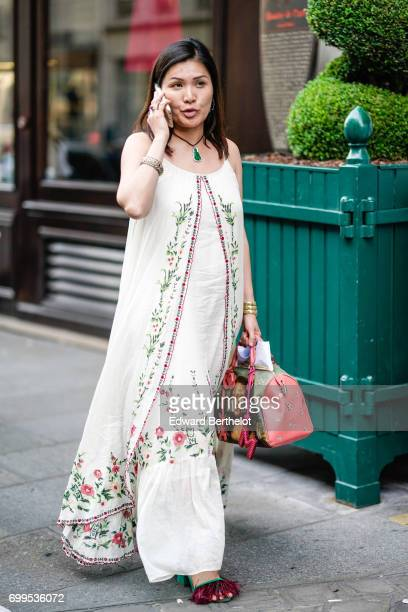 A guest wears a flower print silk outfit shoes with red fringes and a Louis Vuitton bag with the printed portrait of Mona Lisa outside the Haider...