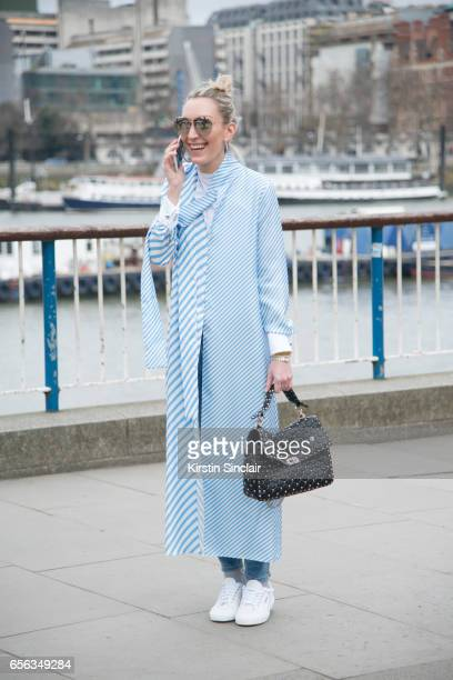 A guest wears a full length shirt jacket Superga trainers Dior sunglasses and a Valentino bag on day 3 of London Womens Fashion Week Autumn/Winter...