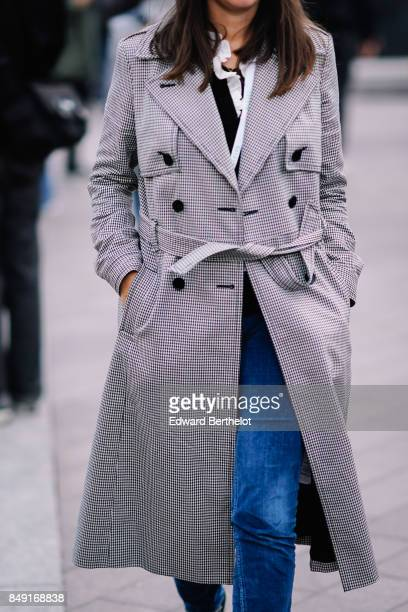 A guest wears a gingham trench coat and blue jeans outside Versus during London Fashion Week September 2017 on September 17 2017 in London England