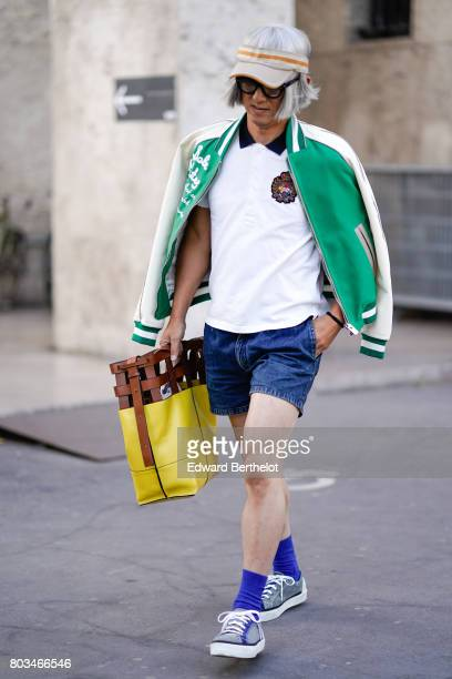 A guest wears a gray cap a green bomber jacket a white polo shirt a blue denim short blue socks sneakers a yellow bag outside the 22/4 Hommes show...