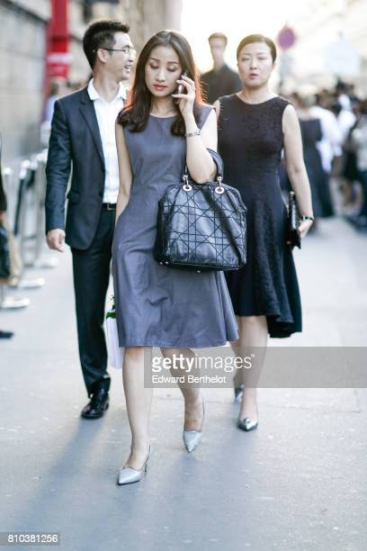 A guest wears a gray dress a Dior bag and silver heels outside the 'Christian Dior couturier du reve' Exhibition Launch celebrating 70 years of...