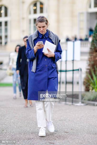 A guest wears a gray pull over a blue coat white pants white sneakers outside Moncler during Paris Fashion Week Womenswear Spring/Summer 2018 on...