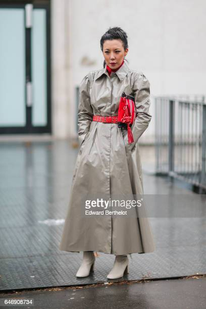 A guest wears a gray rain coat and a red clutch outside the Rochas show during Paris Fashion Week Womenswear Fall/Winter 2017/2018 on March 1 2017 in...