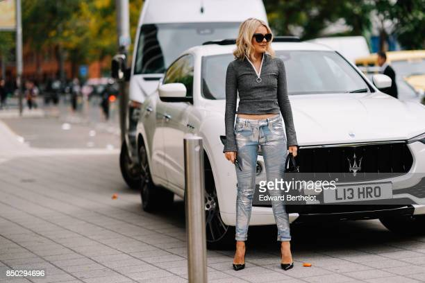 A guest wears a gray top blue jeans black heels during London Fashion Week September 2017 on September 17 2017 in London England