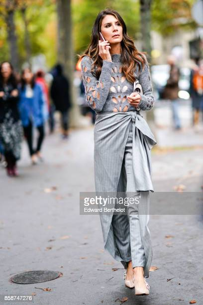 A guest wears a gray top with holes a gray skirt gray pants outside Valentino during Paris Fashion Week Womenswear Spring/Summer 2018 on October 1...