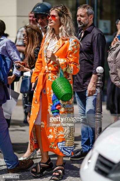 A guest wears a green bag an orange flower print dress striped sandals outside the Jean Paul Gaultier show during Paris Fashion Week Haute Couture...