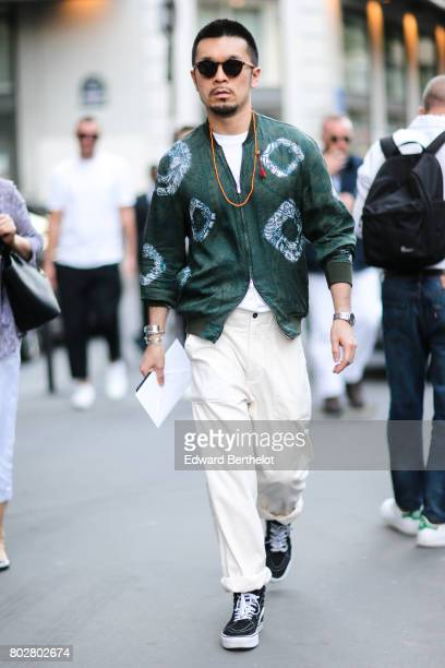 A guest wears a green bomber jacket white pants outside the Hermes show during Paris Fashion Week Menswear Spring/Summer 2018 on June 24 2017 in...