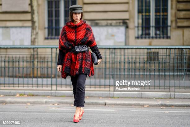 A guest wears a grey hat a wooly red and black turtleneck coat a large black belt a black bag black pants yellow and red shoesoutside the Dries Van...