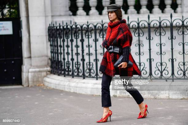 A guest wears a grey hat a wooly turtleneck red and black coat a large black belta black bag black pants yellow and red stilettos outside the Dries...