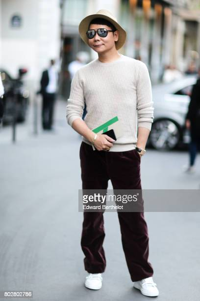 A guest wears a hat a camel pull over velvet pants white shoes outside the Hermes show during Paris Fashion Week Menswear Spring/Summer 2018 on June...