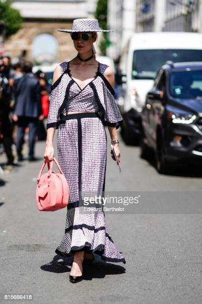 A guest wears a hat a checkered dress a pink bag and black shoes outside the Jean Paul Gaultier show during Paris Fashion Week Haute Couture...