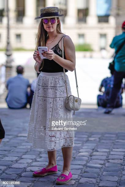 A guest wears a hat purple sunglasses a black lace top a white lace skirt pink shoes outside the Cerruti show during Paris Fashion Week Menswear...