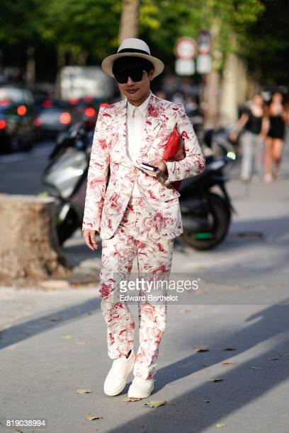 A guest wears a hat sunglasses a blazer jacket suit pants white shoes a red clutch outside the launch party for Chanel's new perfume 'Gabrielle'...