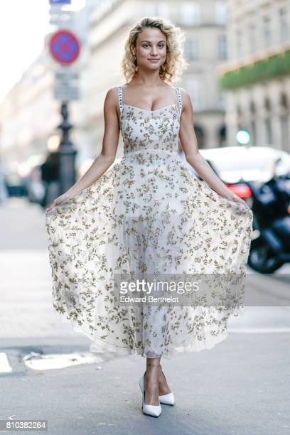 A guest wears a lace mesh dress with golden embroidered flowers and white heels shoes outside the 'Christian Dior couturier du reve' Exhibition...