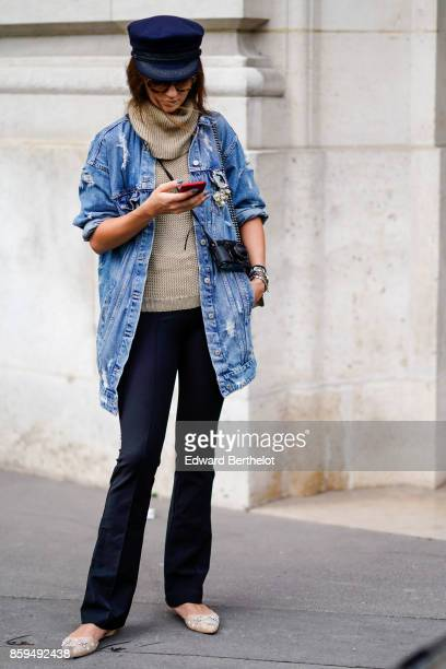 A guest wears a large blue denim jacket a light grey turtleneck pullover black pants and embroidered pumps outside Manish Arora during Paris Fashion...