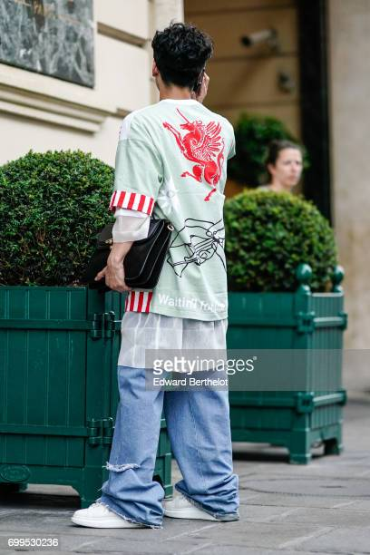 A guest wears a large oversized pull over with several prints including the inscription 'waiting for the revolution a black clutch and oversized blue...