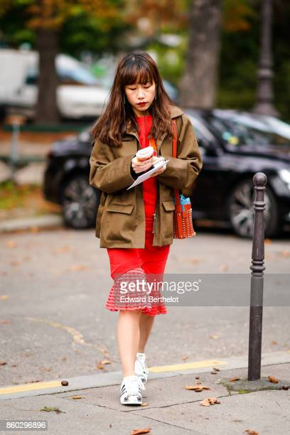 A guest wears a light brown jacket a red studded bag a red dress with pleated hem white sneakers outside Lanvin during Paris Fashion Week Womenswear...
