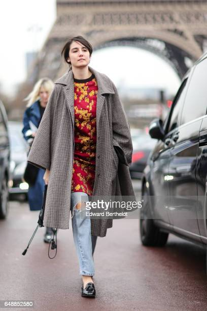 A guest wears a long coat a red top with yellow flower print blue ripped jeans and black shoes outside the Hermes show during Paris Fashion Week...
