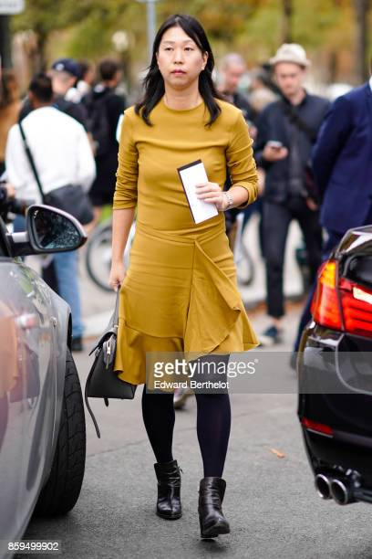 A guest wears a mustard yellow flounced dress black tights black boots outside the Rochas show during Paris Fashion Week Womenswear Spring/Summer...