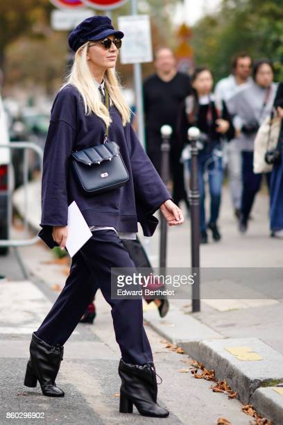 A guest wears a navy blue cap hat a navy blue bag a navy blue top navy blue pants black boots with drawstring outside Lanvin during Paris Fashion...