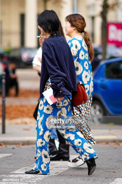 A guest wears a navy blue jacket blue pants with white floral prints a brown bagoutside Lanvin during Paris Fashion Week Womenswear Spring/Summer...