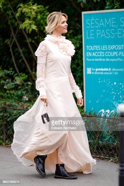 A guest wears a pale pink mousseline long gown with ruffled collar and lace sleeves black reptile skin ankle boots outside Lanvin during Paris...