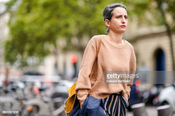 A guest wears a peachcoloured pullover a yellow bag black and white striped pants outside the Dries Van Noten show during Paris Fashion Week...