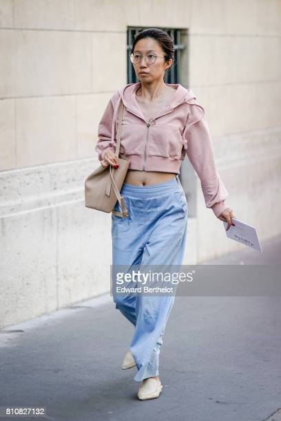 A guest wears a pink bare belly hoodie a bag blue large pants outside the Valentino show during Paris Fashion Week Menswear Spring/Summer 2018 on...