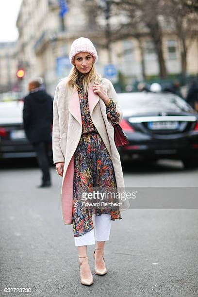 A guest wears a pink beanie hat a pink coat and a floral print dress outside the Jean Paul Gaultier show during Paris Fashion Week Haute Couture...