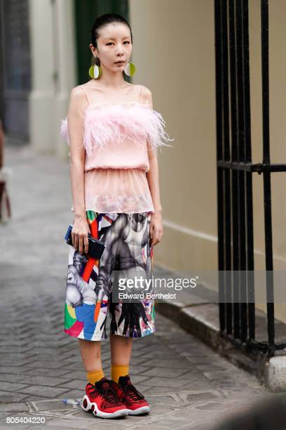 A guest wears a pink fluffy lace tank top multicolor cropped pants orange socks red sneakers shoes after Yohji Yamamoto show during Paris Fashion...