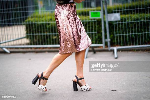 A guest wears a pink lame skirt white and black spotted platform shoes outside Lanvin during Paris Fashion Week Womenswear Spring/Summer 2018 on...