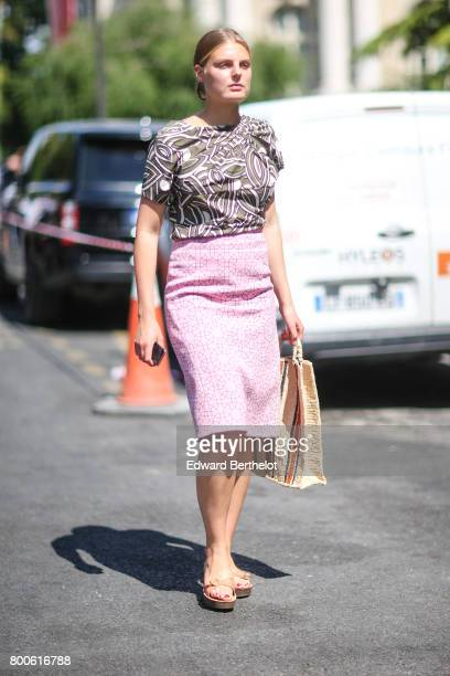 A guest wears a pink skirt a tshirt with prints a straw bag and sandals outside the Dior show during Paris Fashion Week Menswear Spring/Summer 2018...