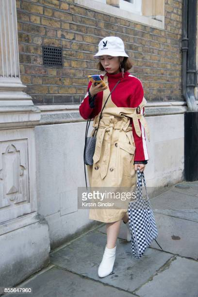 A guest wears a Play boy hat and trench coat dungarees on day 2 of London Womens Fashion Week Spring/Summer 2018 on September 16 2017 in London...