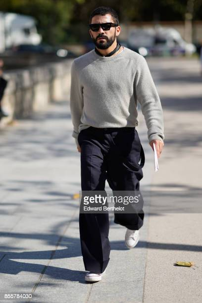 A guest wears a pull over black pants outside Nina Ricci during Paris Fashion Week Womenswear Spring/Summer 2018 on September 29 2017 in Paris France