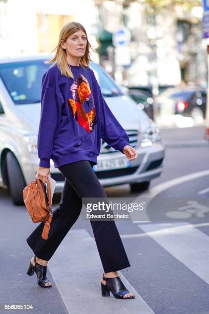 A guest wears a purple pull over with prints a brown bag flare pants shoes outside Acne Studios during Paris Fashion Week Womenswear Spring/Summer...
