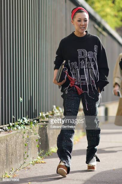 A guest wears a red bandanna a black pull over black pants outside CDG Comme des Garcons during Paris Fashion Week Womenswear Spring/Summer 2018 on...