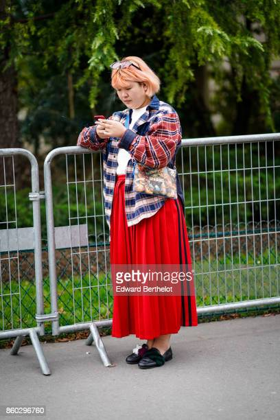 A guest wears a red blue and white checked shirt a long red pleated skirt black moccasins outside Lanvin during Paris Fashion Week Womenswear...