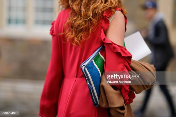 A guest wears a red dress and a multi color striped clutch outside Simone Rocha during London Fashion Week September 2017 on September 16 2017 in...
