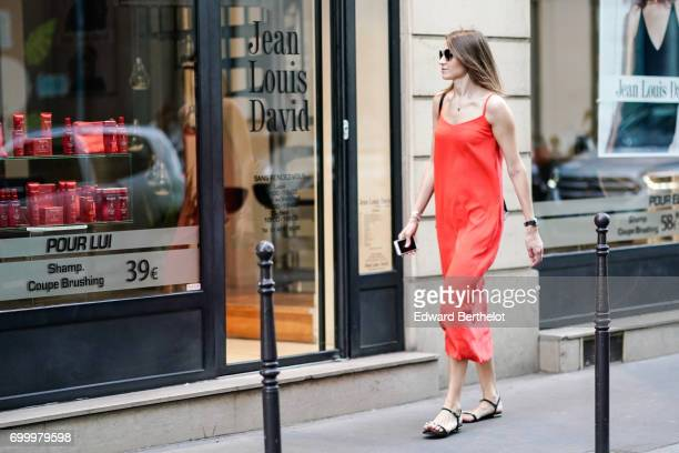 A guest wears a red dress outside the OAMC show during Paris Fashion Week Menswear Spring/Summer 2018 on June 21 2017 in Paris France