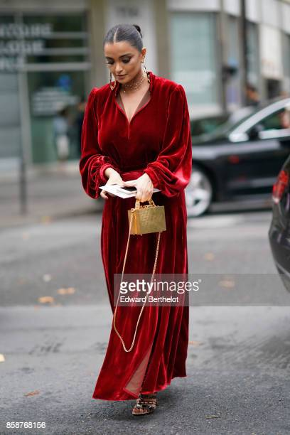A guest wears a red dress outside Valentino during Paris Fashion Week Womenswear Spring/Summer 2018 on October 1 2017 in Paris France