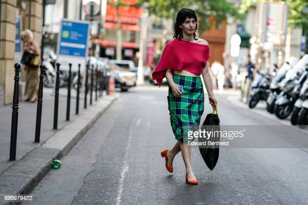 A guest wears a red off shoulder top and a green tartan skirt and red shoes outside the OAMC show during Paris Fashion Week Menswear Spring/Summer...