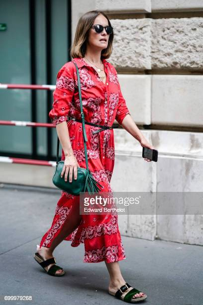 A guest wears a red outfit and a green bag outside the OAMC show during Paris Fashion Week Menswear Spring/Summer 2018 on June 21 2017 in Paris France