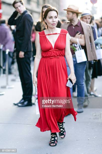 A guest wears a red ruffled dress outside the 'Christian Dior couturier du reve' Exhibition Launch celebrating 70 years of creation at Musee Des Arts...